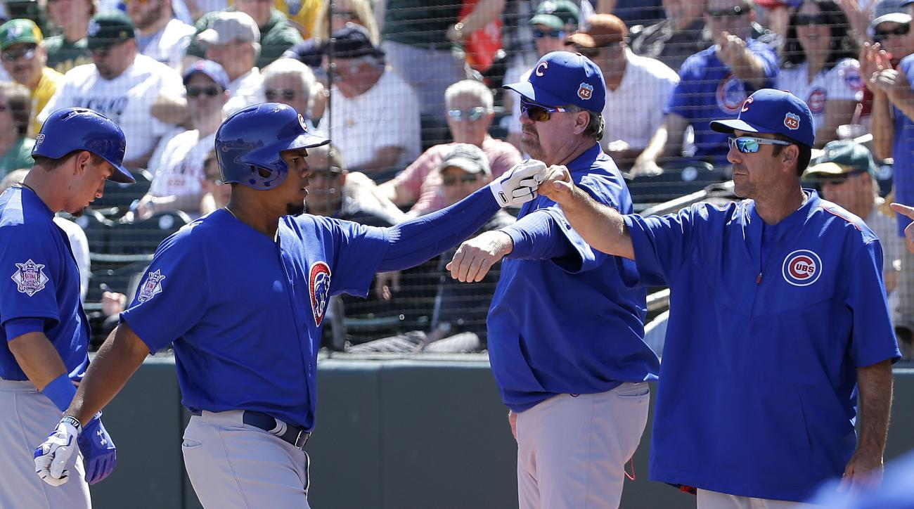 Chicago Cubs' Jeimer Candelario, left, is congratulated after hitting a solo home run against the Oakland Athletics during the first inning of a spring training baseball game in Mesa, Ariz., Sunday, March 13, 2016. (AP Photo/Jeff Chiu)