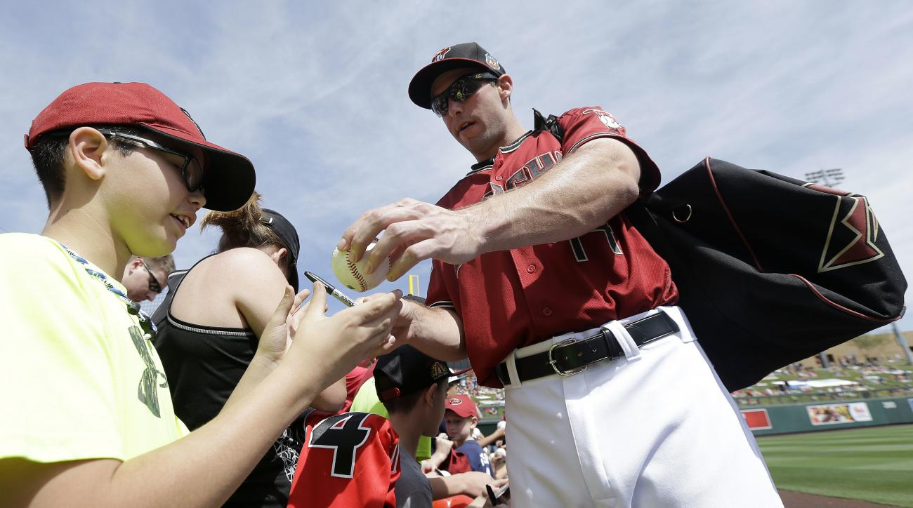 Arizona Diamondbacks first baseman Paul Goldschmidt, right, signs autographs for fans before a spring training baseball game between the Diamondbacks and the Seattle Mariners in Scottsdale, Ariz., Monday, March 14, 2016. (AP Photo/Jeff Chiu)