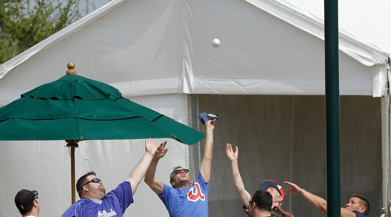 Fans try to catch a foul ball during a spring training baseball game between the Atlanta Braves and the Miami Marlins, Friday, March 18, 2016, in Kissimmee, Fla. (AP Photo/John Raoux)