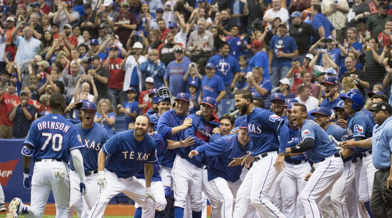 Texas Rangers' Lewis Brinson (70) celebrates his winning home run with teammates as he runs to home plate in the bottom of the ninth inning during a spring exhibition baseball game against the Kansas City Royals, Friday, March 18, 2016, in San Antonio. (A