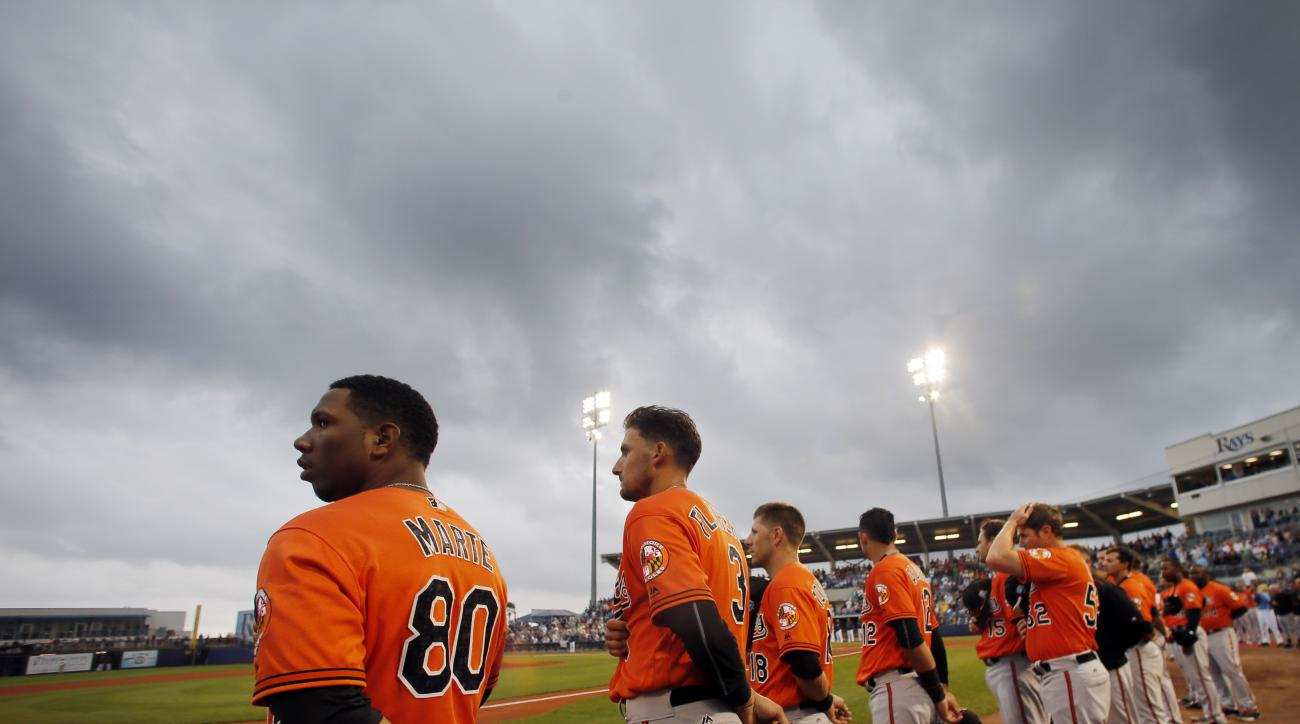 Baltimore Orioles' Alfredo Marte (80), Ryan Flaherty (3) and the rest of the team line up for the playing of the national anthem before a spring training baseball game against the Tampa Bay Rays on Saturday, March 19, 2016, in Port Charlotte, Fla. The gam