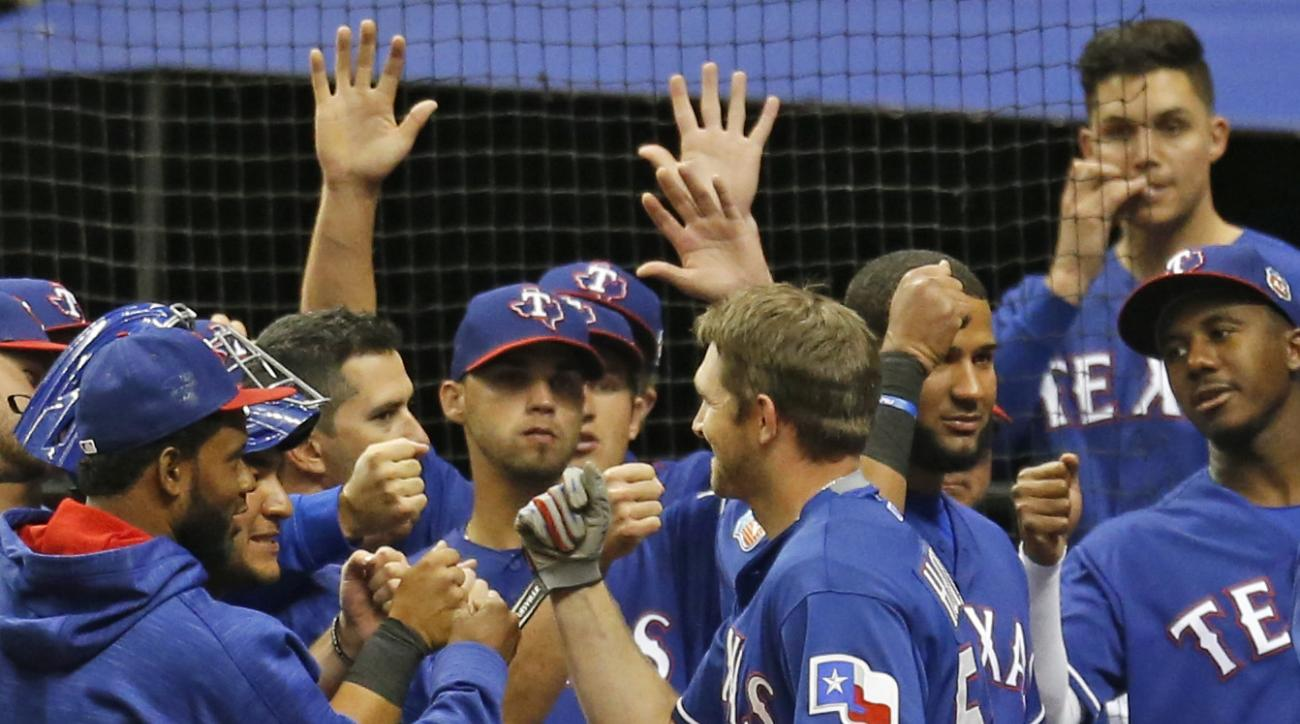 Texas Rangers Jared Hoying celebrates his home run with teammates in a spring training baseball game against the Kansas City Royals, Saturday, March 19, 2016 in San Antonio.  (AP Photo/Ronald Cortes)