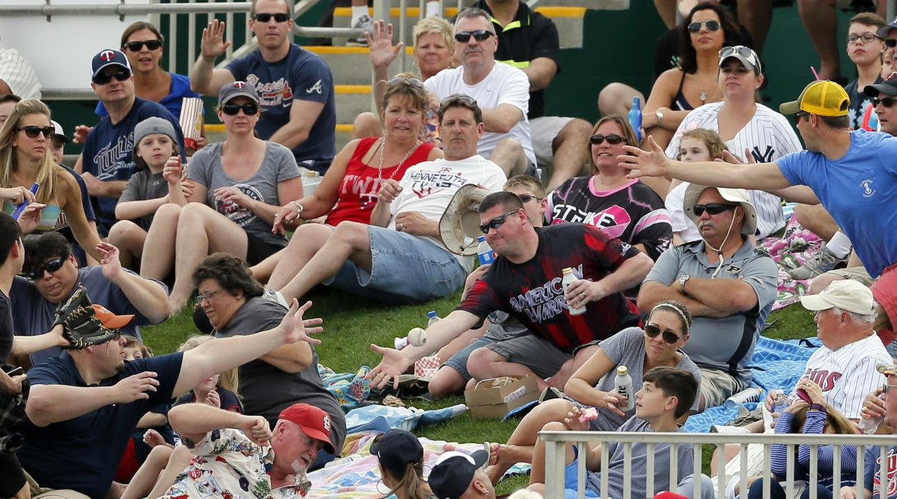 Fans sitting along the right field fence scatter as another reaches out for a foul ball that came off the bat of Minnesota Twins' Trevor Plouffe in the first inning of a spring training baseball game against the New York Yankees on Sunday, March 20, 2016,