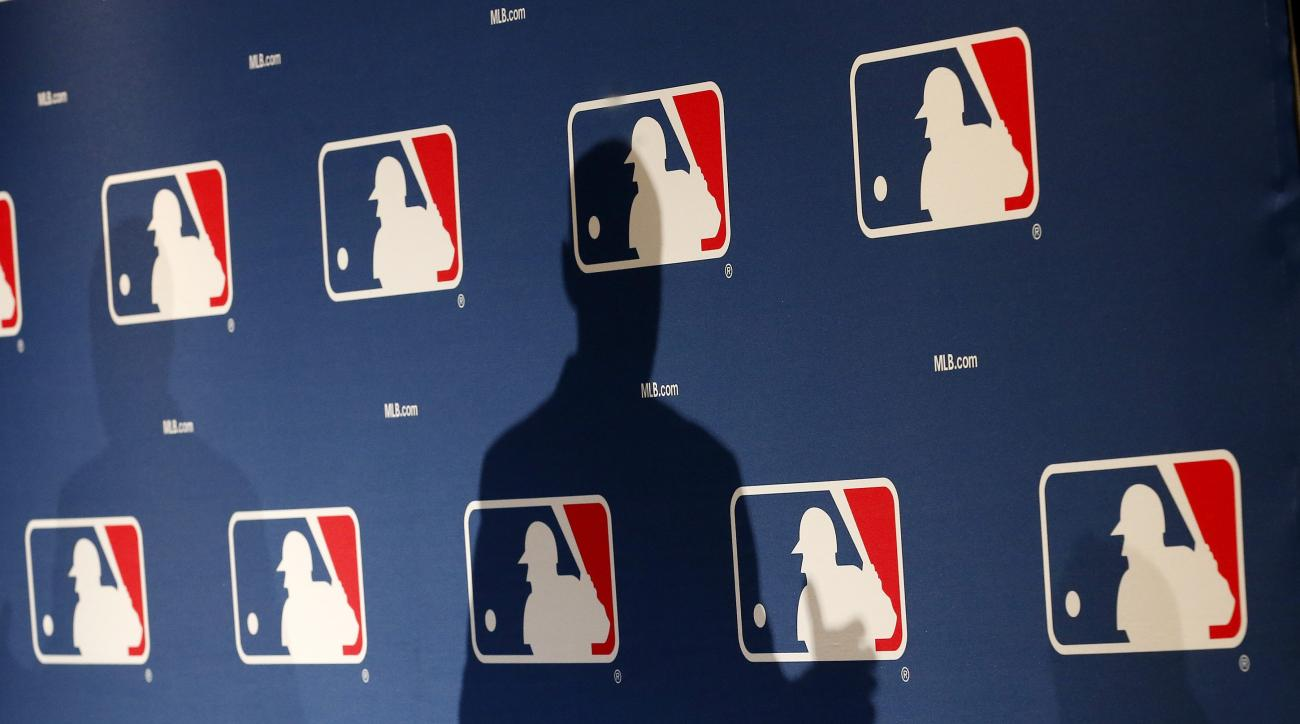 FILE - In this Monday, Feb. 23, 2015 file photo, the shadow of MLB Commissioner Rob Manfred is projected on an MLB logo backdrop in Phoenix. Major league teams steeply increased the money spent on young players in 2015, but the overall percentage of reven