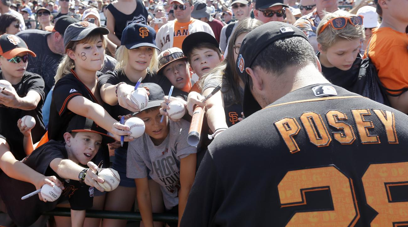 San Francisco Giants catcher Buster Posey gives autographs to fans before a spring training baseball game against the Oakland Athletics in Scottsdale, Ariz., Monday, March 21, 2016. (AP Photo/Jeff Chiu)