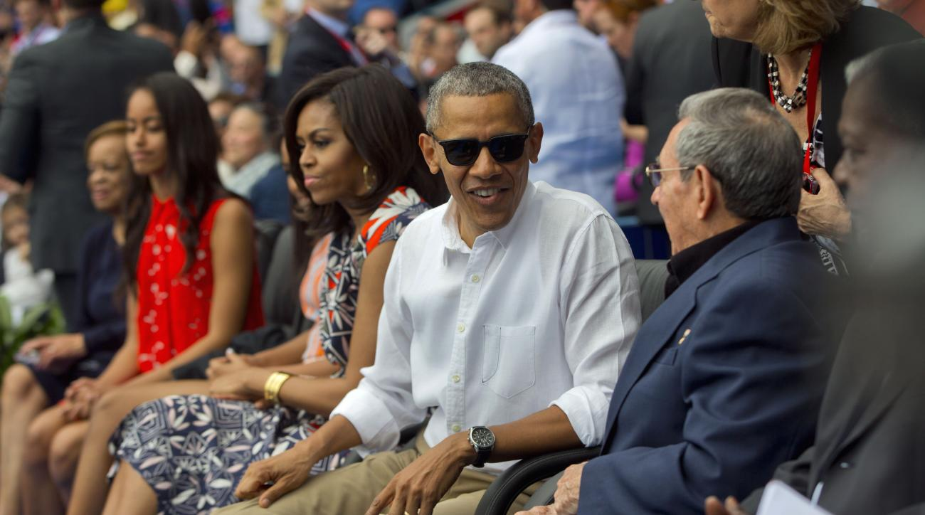 President Barack Obama, with members of the first family, talks with Cuban President Raul Castro as they attend an exhibition baseball game between the Tampa Bay Rays and the Cuban National team at the Estadio Latinoamericano, Tuesday, March 22, 2016, in