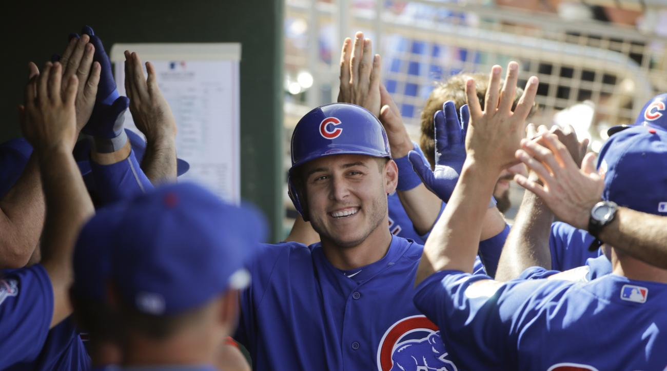Chicago Cubs' Anthony Rizzo, center, celebrates his two-run home run in the dugout during the sixth inning of a spring training baseball game against the Cincinnati Reds, Tuesday, March 22, 2016, in Goodyear, Ariz. (AP Photo/Jae C. Hong)