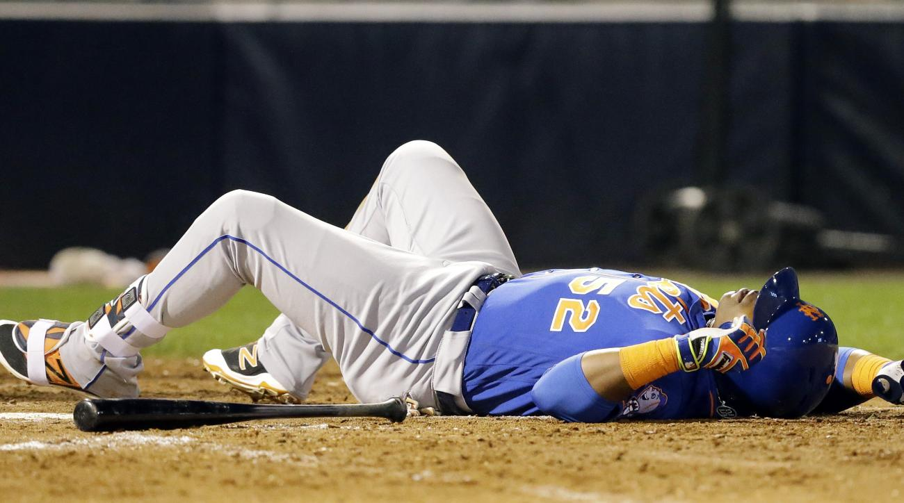 New York Mets' Yoenis Cespedes goes down after fouling a pitch from New York Yankees' Aroldis Chapman off his foot during the fifth inning of a spring training baseball game Tuesday, March 22, 2016, in Tampa, Fla. Cespedes stayed in the game. (AP Photo/Ch