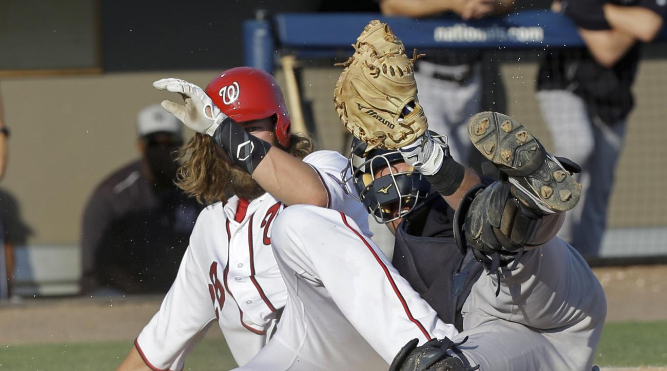 New York Yankees catcher Austin Romine is upended by Washington Nationals' Jayson Werth, left, at home plate but makes the tag for the out in the third inning spring training baseball game, Wednesday, March 23, 2016, in Viera, Fla. (AP Photo/John Raoux)