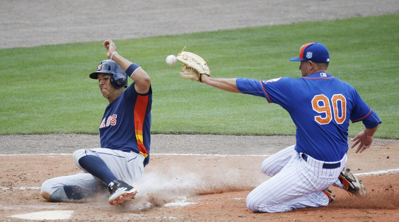 Houston Astros' Carlos Correa, safely slides into home plate after a wild pitch by New York Mets' Beck Wheeler, during the fourth inning of an exhibition spring training baseball game, Thursday, March 24, 2016, in Port St. Lucie, Fla. (AP Photo/Brynn Ande