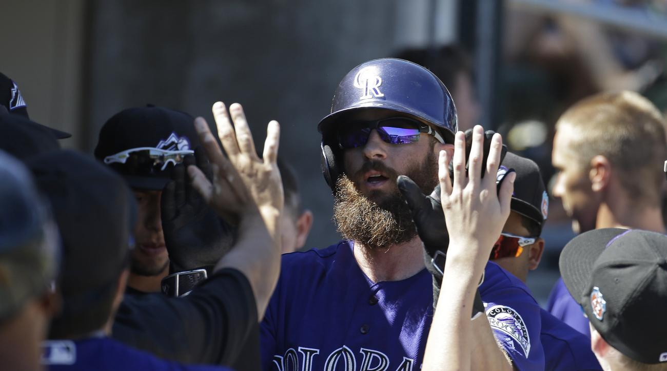 Colorado Rockies' Charlie Blackmon is congratulated after scoring during the first inning of a spring training baseball game against the Seattle Mariners, Thursday, March 24, 2016, in Scottsdale, Ariz. (AP Photo/Darron Cummings)