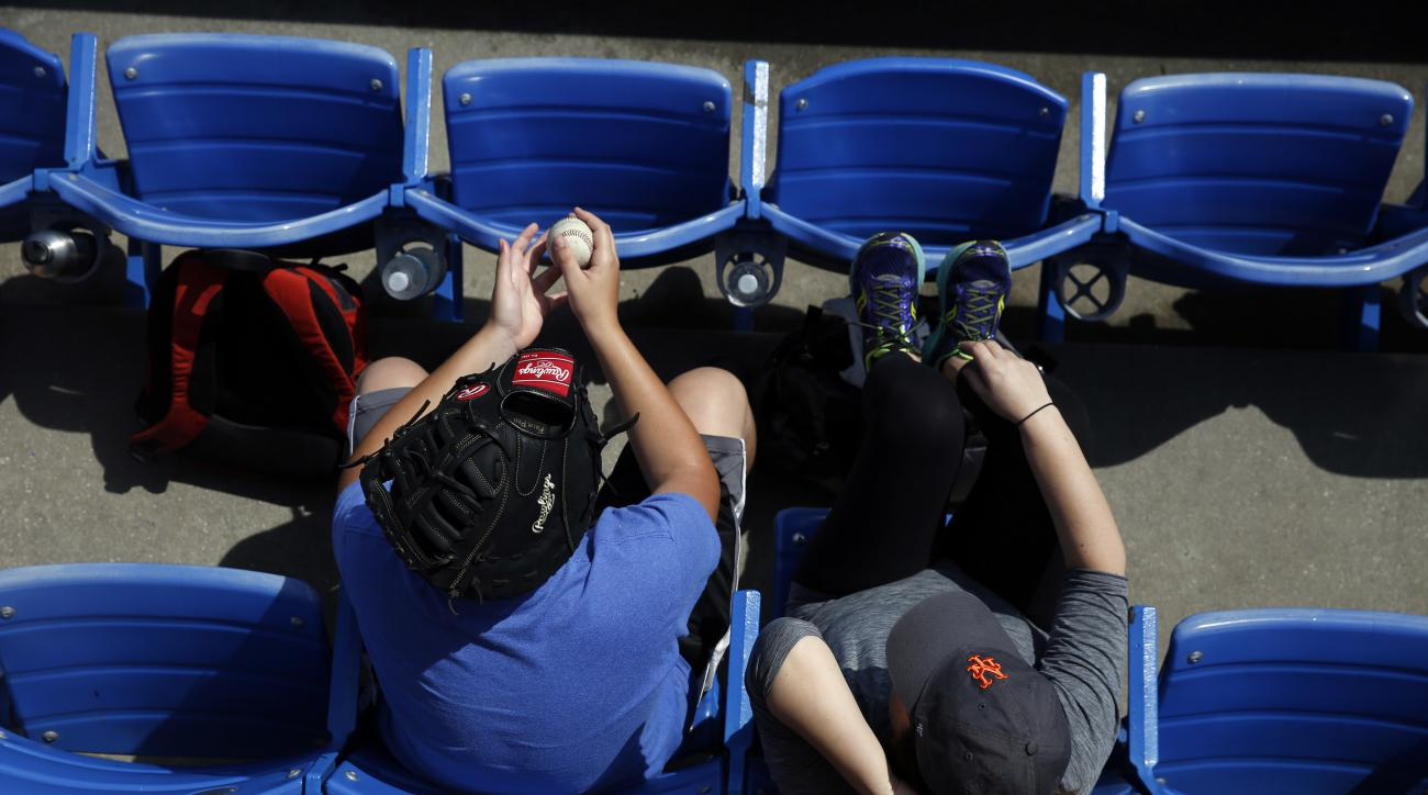 Fans sit in the stands and wait for the St. Louis Cardinals to play the New York Mets in an exhibition spring training baseball game, Friday, March 25, 2016, in Port St. Lucie, Fla. (AP Photo/Brynn Anderson)