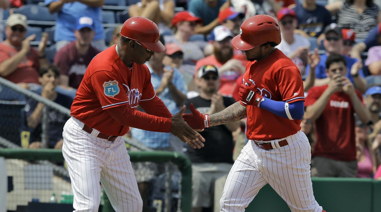 Philadelphia Phillies' Freddy Galvis, right, shakes hands with third base coach Juan Samuel after his home run off Detroit Tigers starting pitcher Justin Verlander during the fifth inning of a spring training baseball game Saturday, March 26, 2016, in Cle