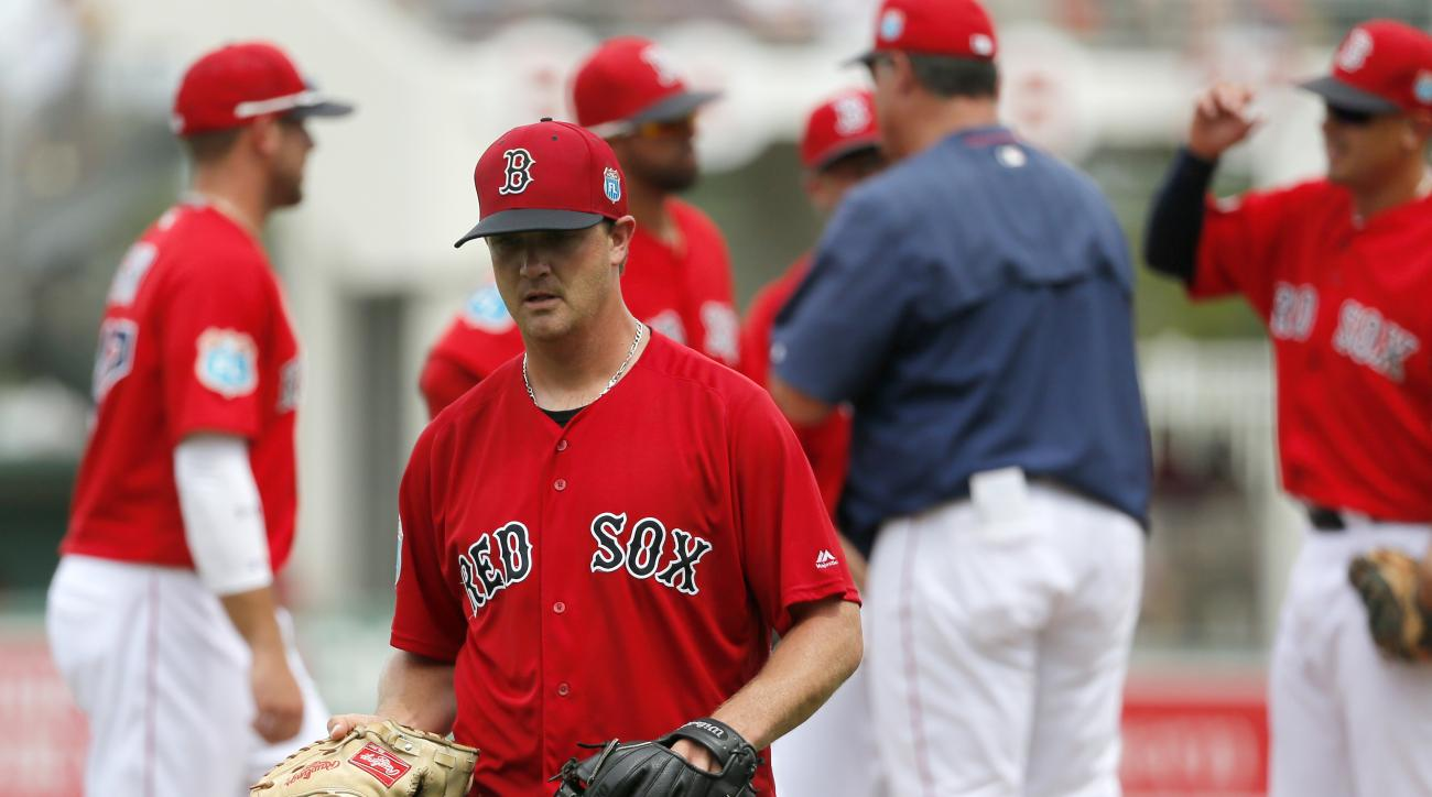 Boston Red Sox starting pitcher Steven Wright carries catcher Ryan Hanigan's backup glove while leaving in the sixth inning of an interleague spring training baseball game against the Philadelphia Phillies on Sunday, March 27, 2016, in Sarasota, Fla. (AP