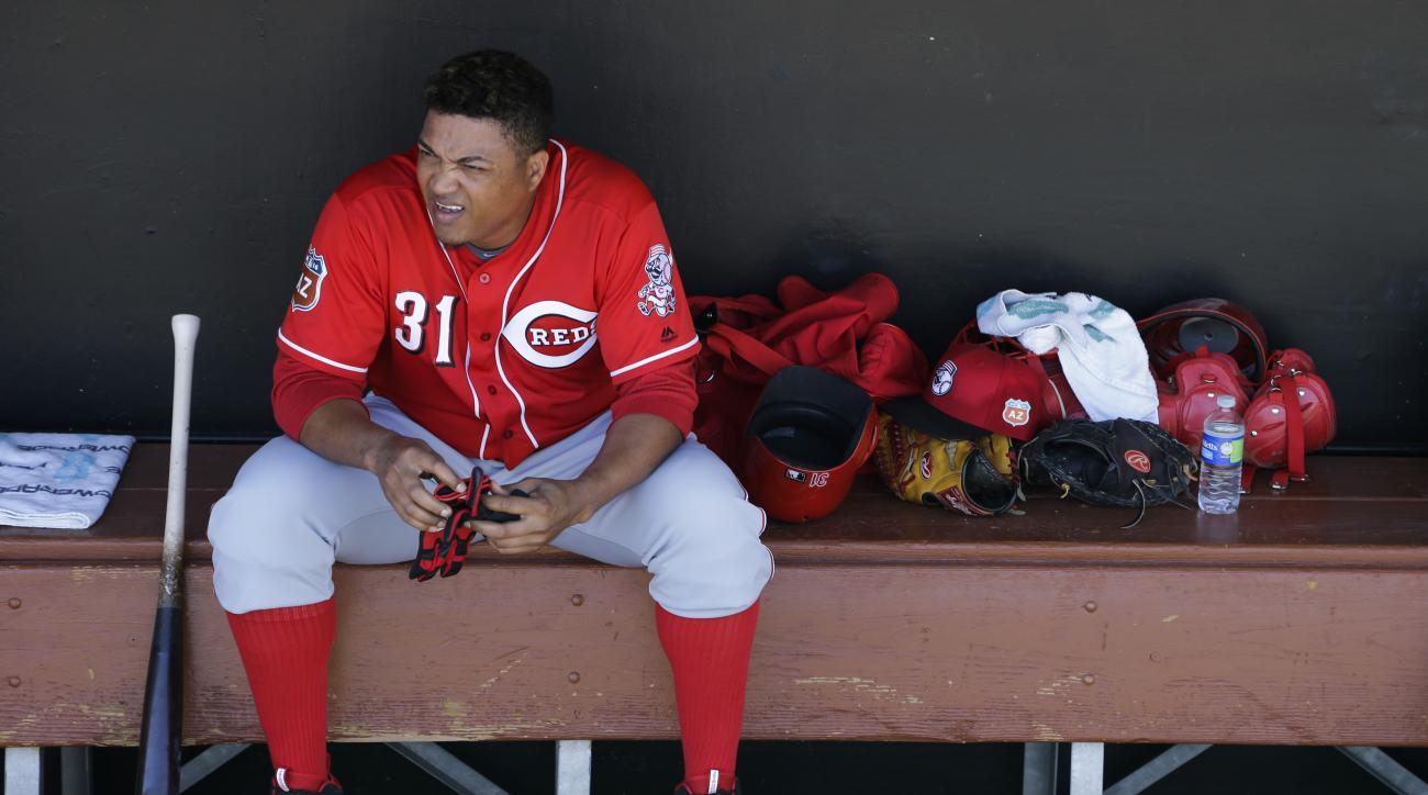 Cincinnati Reds starting pitcher Alfredo Simon sits in the dugout before the team's spring training baseball game against the Los Angeles Dodgers, Sunday, March 27, 2016, in Phoenix. (AP Photo/Jae C. Hong)