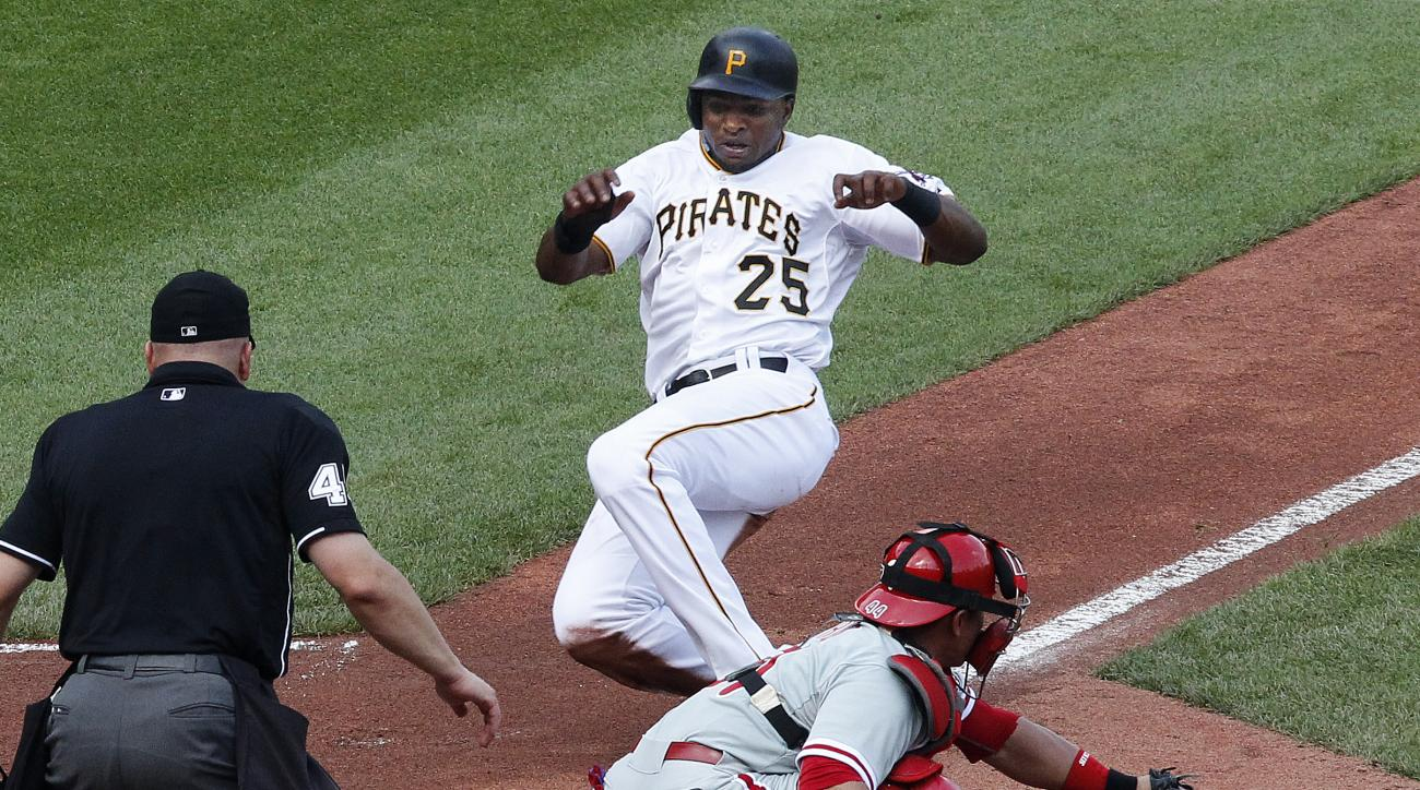 In this June 13, 2015 photo, Pittsburgh Pirates' Gregory Polanco (25) begins his slide as the ball bounces off the glove of Philadelphia Phillies catcher Carlos Ruiz during the first inning of a baseball game in Pittsburgh. Retired World Series-winning ca