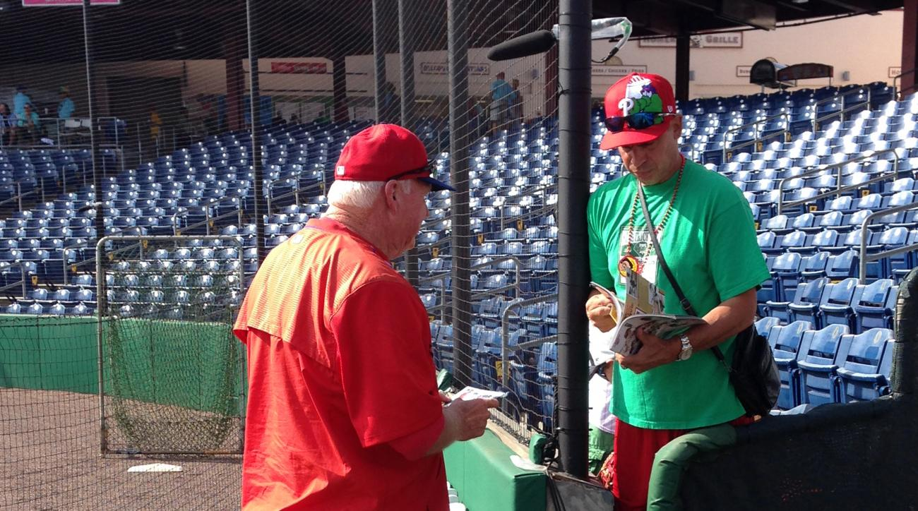 In this photo taken March 17, 2016, former Philadelphia Phillies manager Charlie Manuel, left, now a senior adviser for the team and a guest instructor in spring training, gives an autograph to a fan before the Phillies play the Tampa Bay Rays in a baebal