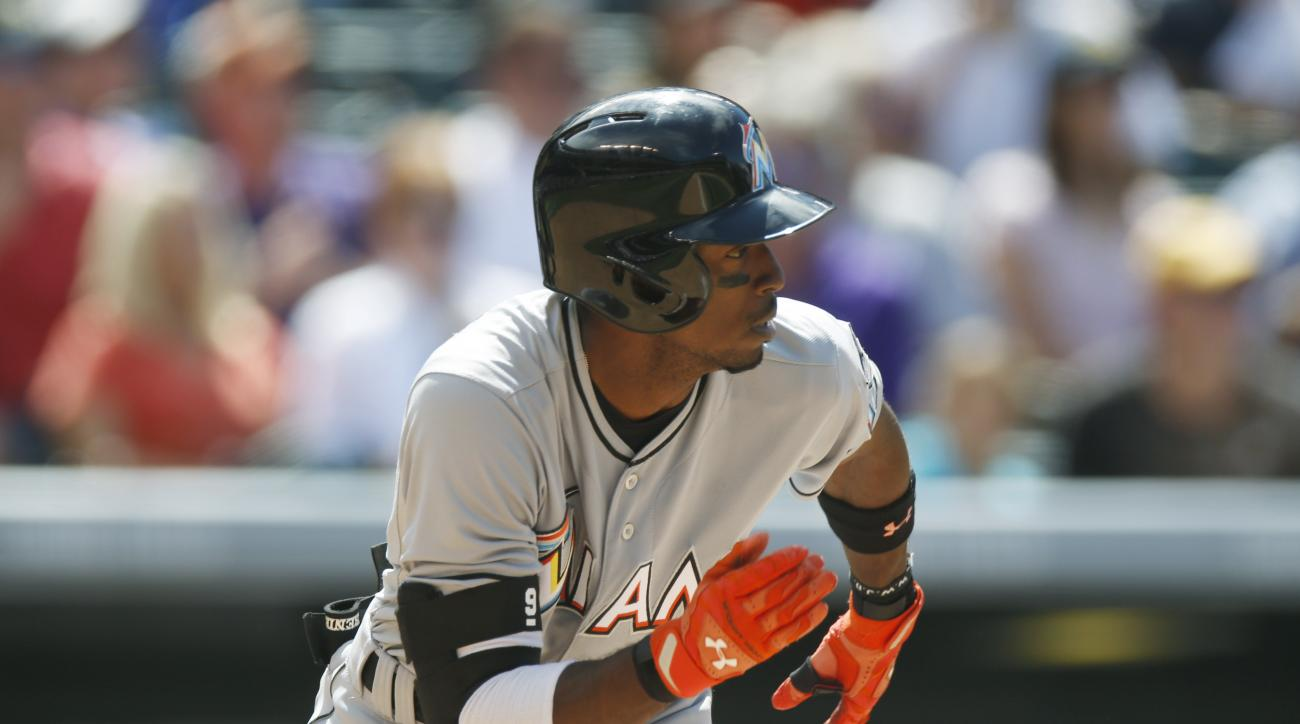 FILE - In this June 7, 2015, file photo, Miami Marlins' Dee Gordon runs after hitting a single against the Colorado Rockies in the fifth inning of a baseball game in Denver. Marlins leadoff hitter Gordon says he is a better batter since he stopped trying