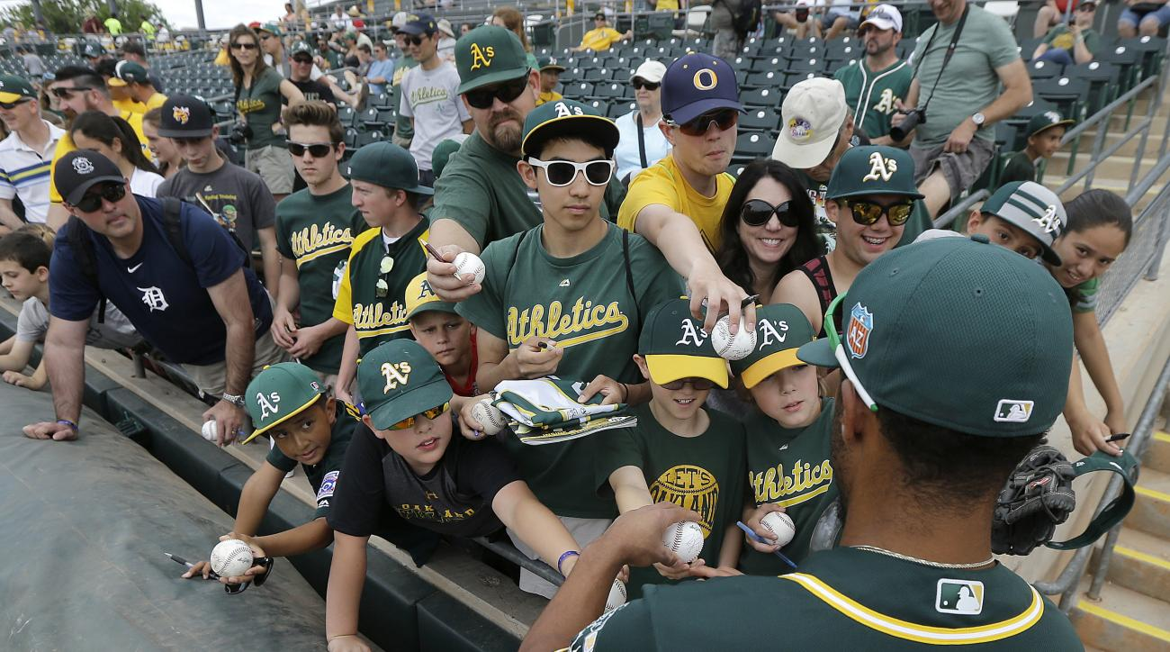 Oakland Athletics shortstop Marcus Semien, foreground, gives autographs to fans before a spring training baseball game against the Cleveland Indians in Mesa, Ariz., Monday, March 28, 2016. (AP Photo/Jeff Chiu)