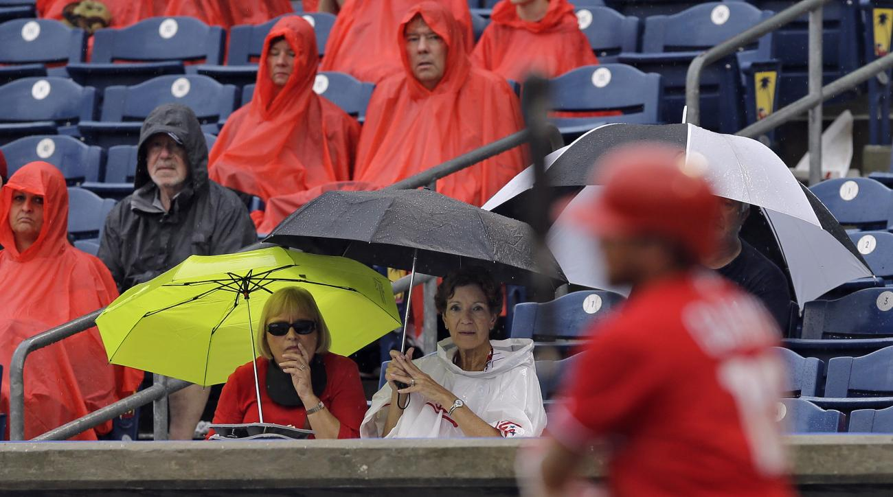 Fans sit in the rain as the Philadelphia Phillies bat against the New York Yankees during the fourth inning of a spring training baseball game Tuesday, March 29, 2016, in Clearwater, Fla. The game was called after the inning. (AP Photo/Chris O'Meara)