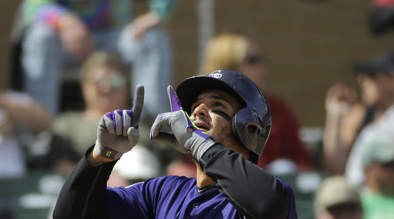 Colorado Rockies' Nolan Arenado, center, gestures skyward as he scores after hitting his second home run of the game during the fifth inning of a spring training baseball game against the Arizona Diamondbacks Tuesday, March 29, 2016, in Scottsdale, Ariz.