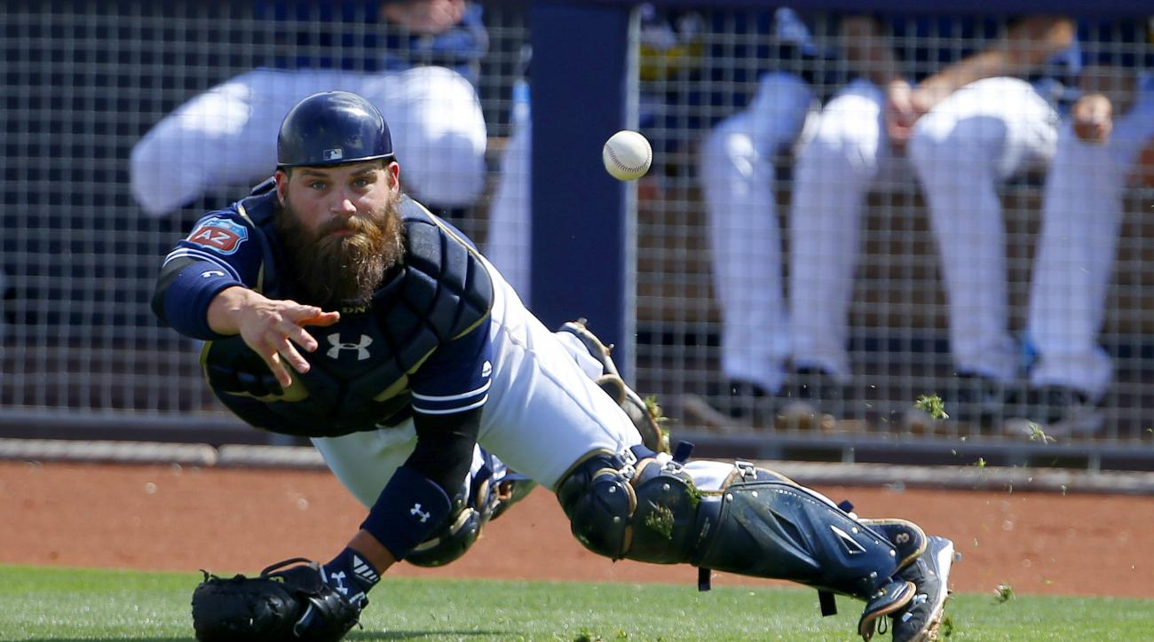 San Diego Padres' Derek Norris tosses the baseball to pitcher Colin Rea covering home plate after a pitch got away from Norris during the fourth inning of a spring training baseball game Tuesday, March 29, 2016, in Peoria, Ariz.  Los Angeles Dodgers runne
