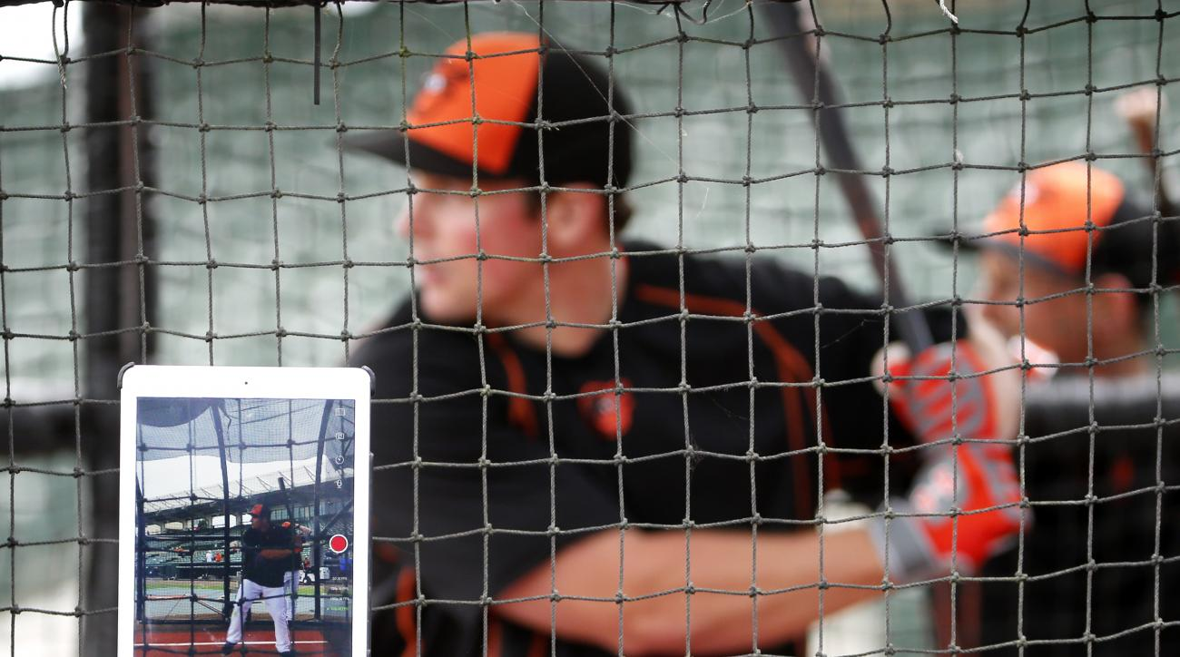 Baltimore Orioles' Travis Snider takes video of his swings with his IPAD during batting practice before a spring training exhibition baseball game against the Boston Red Sox in Sarasota, Fla., Saturday, March 7, 2015.  (AP Photo/Gene J. Puskar)