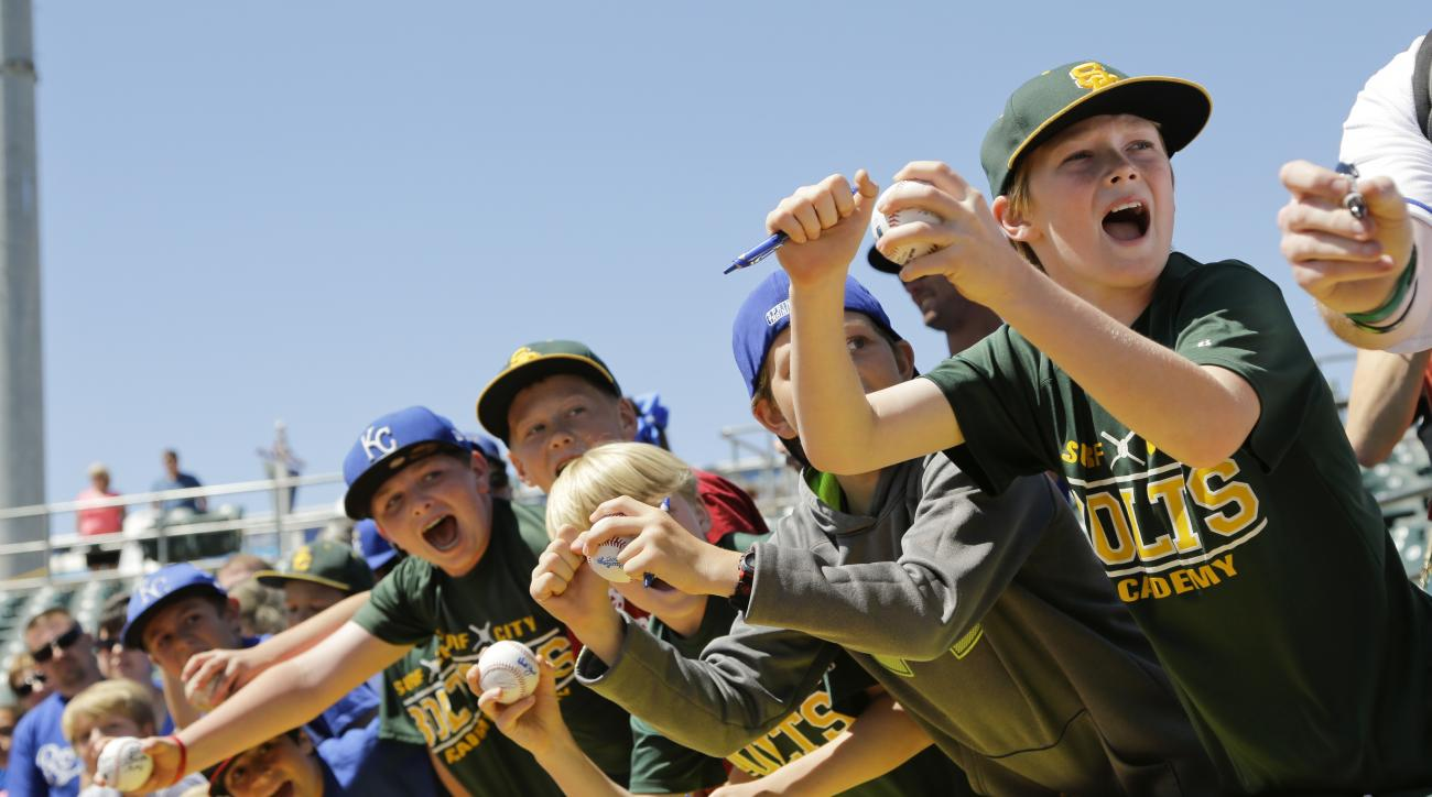 Young baseball fans scream to get autographs from Kansas City Royals players before the team's spring training baseball game against the Texas Rangers Wednesday, March 30, 2016, in Surprise, Ariz. (AP Photo/Jae C. Hong)