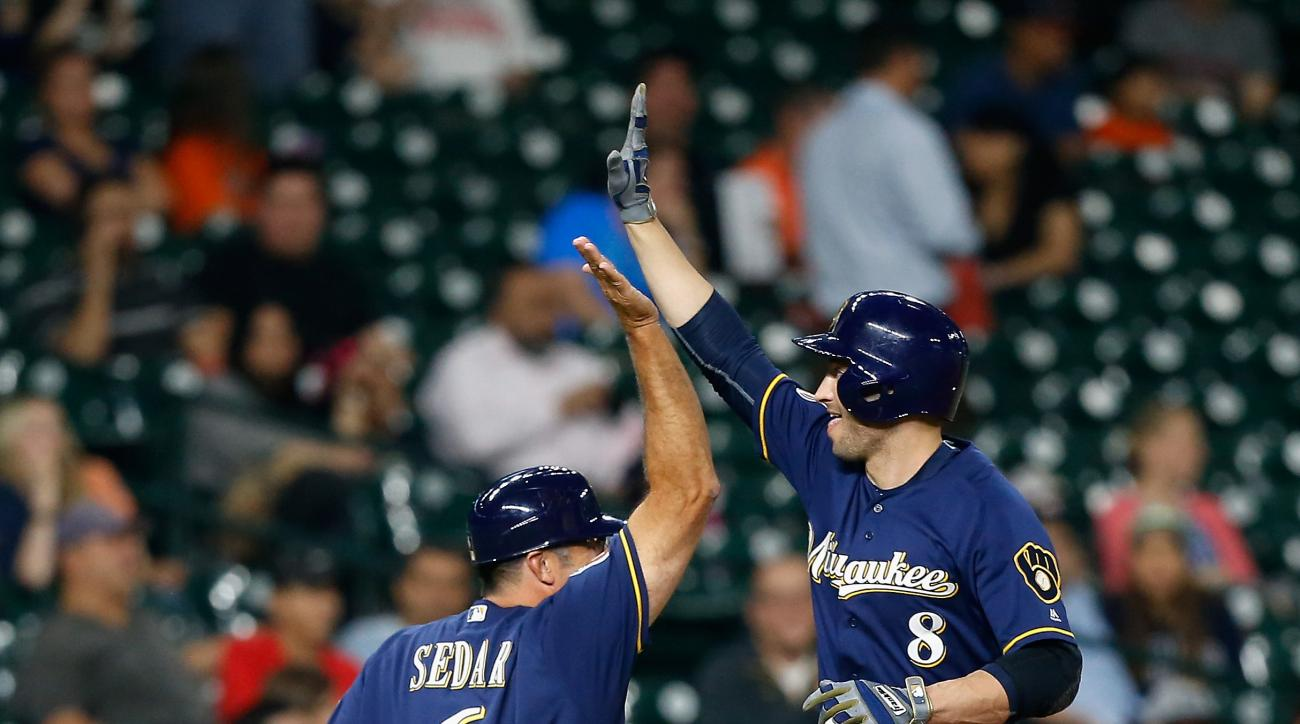 Milwaukee Brewers' Ryan Braun (8) receives a high five from third base coach Ed Sedar (6) after hitting a home run in the second inning against the Houston Astros during a spring training baseball game Thursday, March 31, 2016, in Houston. (AP Photo/Bob L