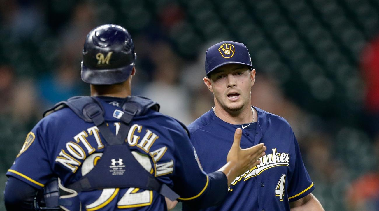 Milwaukee Brewers' Corey Knebel (46) shakes hands with catcher Jacob Nottingham (92) after the final out against the Houston Astros during a spring training baseball game Thursday, March 31, 2016, in Houston. Milwaukee won 6-1. (AP Photo/Bob Levey)