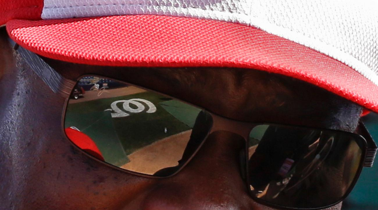 FILE - In this March 23, 2016, file photo, the team logo on the playing field is reflected in the sunglasses of Washington Nationals manager Dusty Baker as he talks with players during batting practice before a spring training baseball game against the Ne