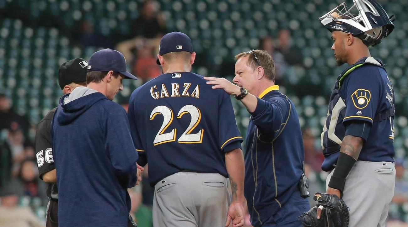 Milwaukee Brewers pitcher Matt Garza is looked at by a trainer before being taken out in the fourth inning of a exhibition baseball game against the Houston Astros, Friday, April 1, 2016 in Houston.  (AP Photo/Richard Carson)