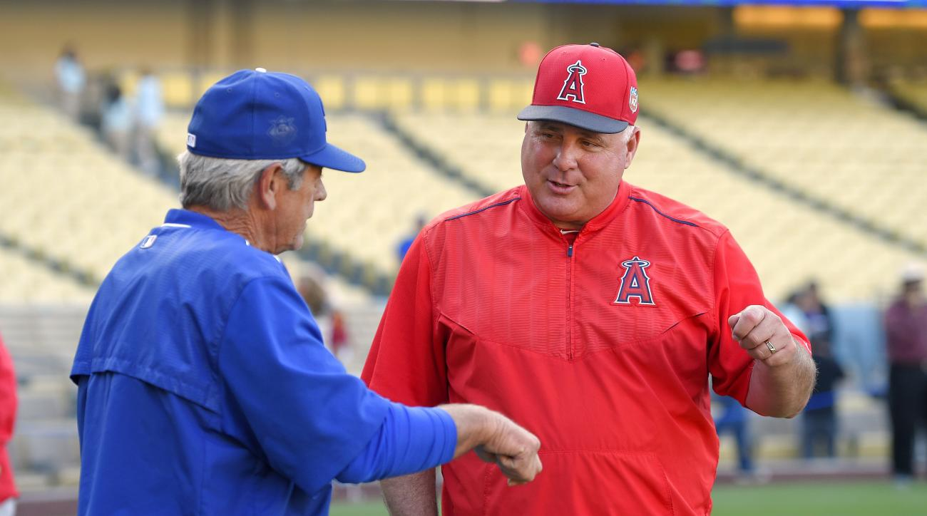 Los Angeles Dodgers catching coach Steve Yeager, left, and Los Angeles Angels manager Mike Scioscia talk during warm-ups prior to an exhibition baseball game, Friday, April 1, 2016, in Los Angeles. (AP Photo/Mark J. Terrill)