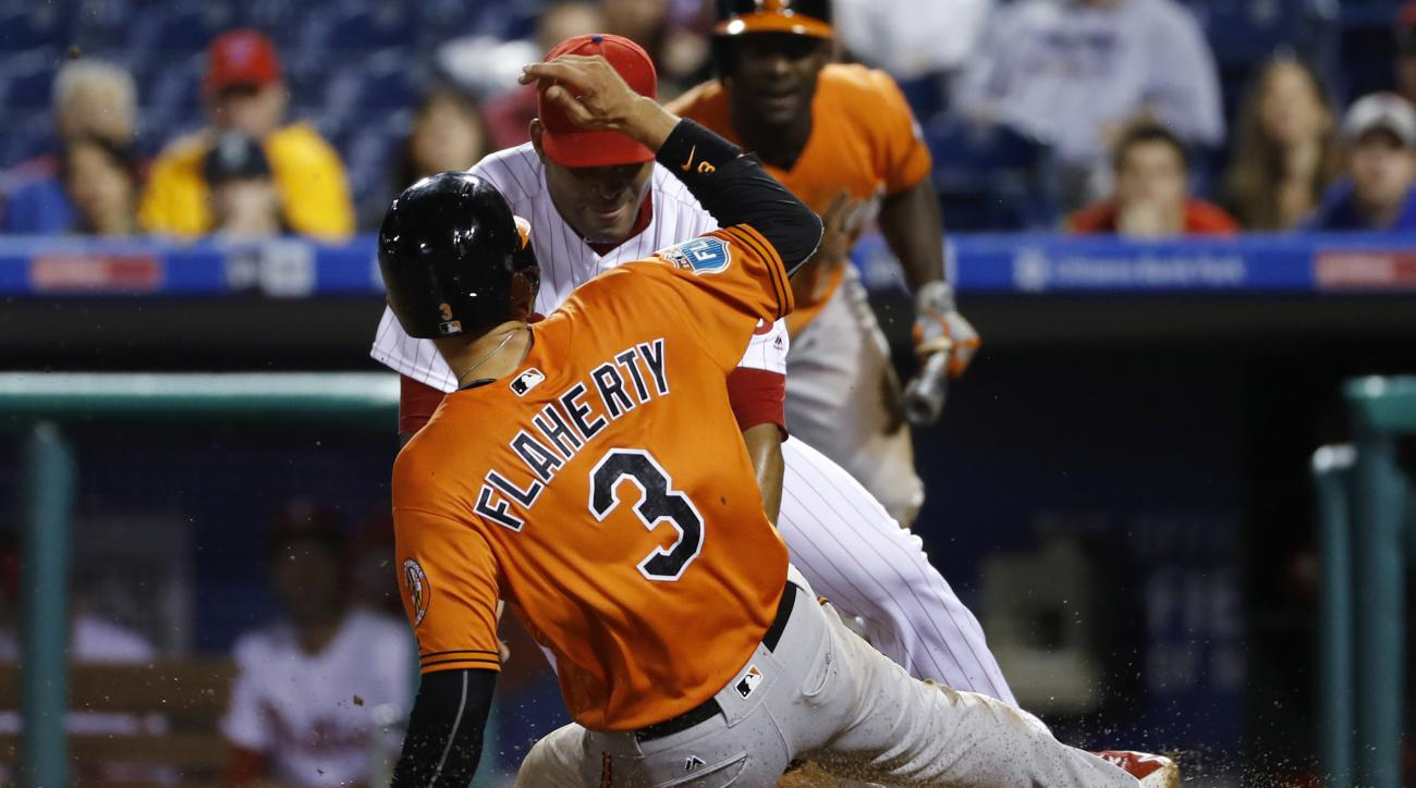 Baltimore Orioles' Ryan Flaherty scores the go-ahead run past Philadelphia Phillies relief pitcher Dalier Hinojosa on a wild pitch during the ninth inning of an exhibition baseball game, Friday, April 1, 2016, in Philadelphia. Baltimore won 8-7. (AP Photo