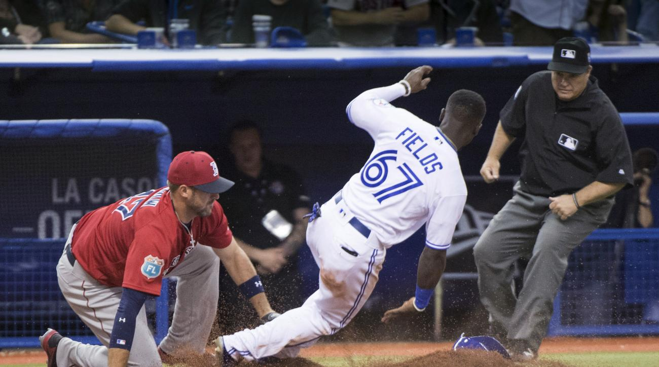 Toronto Blue Jays' Roemon Fields is tagged out while trying to steal third by Boston Red Sox third baseman Travis Shaw as umpire Toby Basner watches during the ninth inning of an exhibition baseball game Friday, April 1, 2016, in Montreal. (Paul Chiasson/