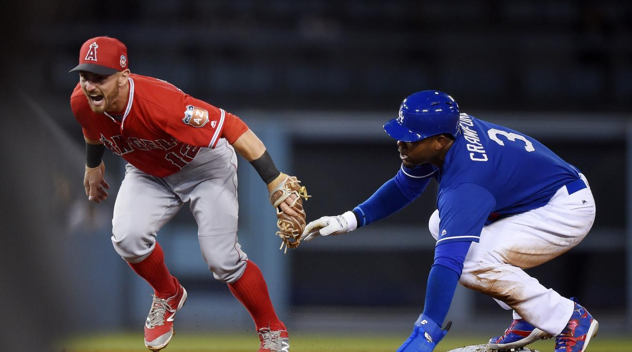 Los Angeles Angels second baseman Johnny Giavotella, left, reacts after tagging out Los Angeles Dodgers' Carl Crawford at second as Crawford tried to steal during the second inning of an exhibition baseball game Friday, April 1, 2016, in Los Angeles. (AP