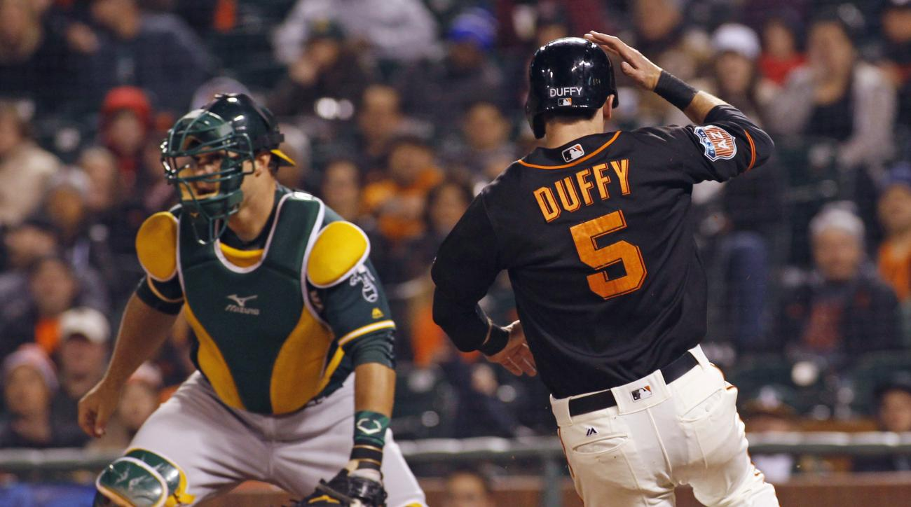 San Francisco Giants' Matt Duffy scores on a Gregor Blanco single as Oakland Athletics' Josh Phegley awaits a throw during the seventh inning of an exhibition baseball game, Friday, April 1, 2016, in San Francisco. (AP Photo/George Nikitin)