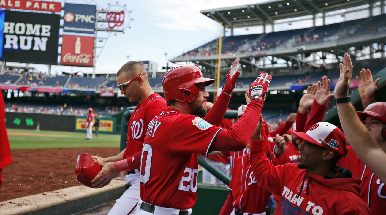 Washington Nationals' Daniel Murphy (20) is congratulated at the dugout after hitting a solo home run during the first inning of an exhibition baseball game against the Minnesota Twins at Nationals Park, Saturday, April 2, 2016, in Washington. (AP Photo/A