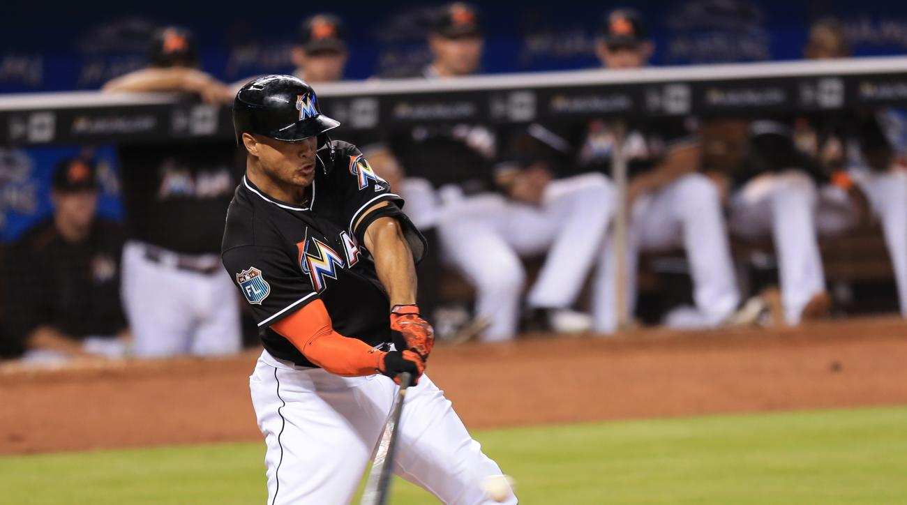 Miami Marlins' Giancarlo Stanton hits an RBI single to score Marcell Ozuna  from third base during the third inning of an exhibition baseball game against the New York Yankees on Saturday, April 2, 2016, in Miami. (AP Photo/Rob Foldy)