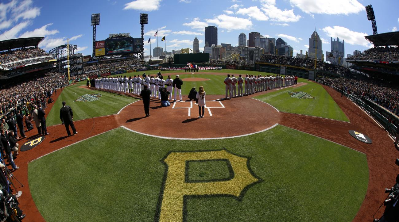 The Pittsburgh Pirates and the St. Louis Cardinals stand on the baselines for the national anthem at the first baseball game of the Major League season at PNC Park in Pittsburgh, Sunday, April 3, 2016. (AP Photo/Gene J. Puskar)