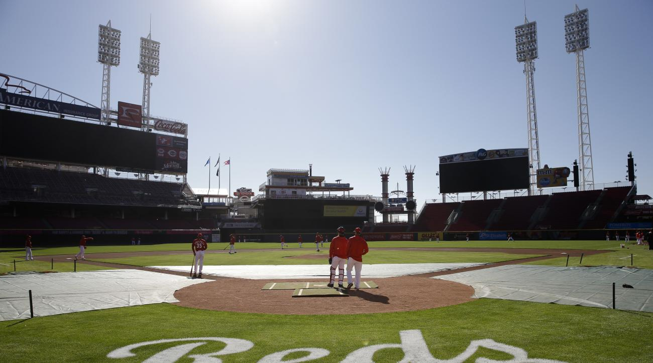 The Cincinnati Reds stand on the field during practice at Great American Ballpark, Sunday, April 3, 2016, in Cincinnati. (AP Photo/John Minchillo)