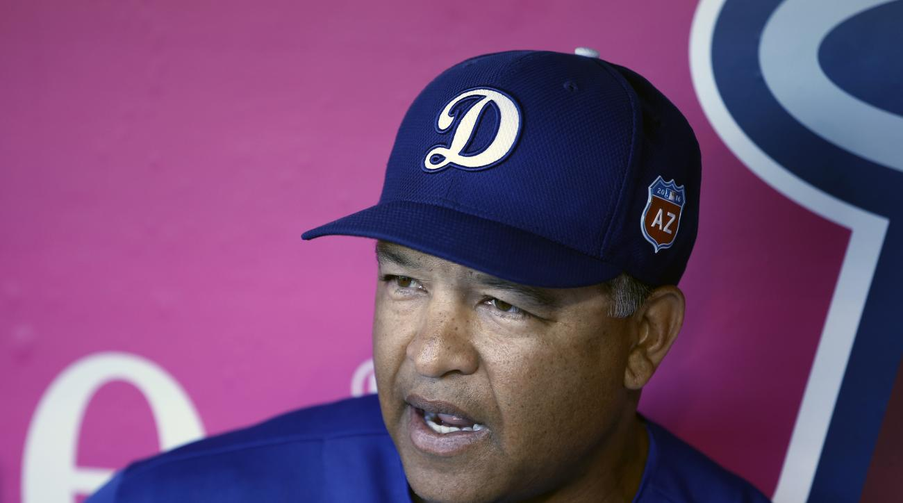 FILE - In this April 2, 2016, file photo, Los Angeles Dodgers manager Dave Roberts talks to members of the media from the dugout before a spring exhibition baseball game against the Los Angeles Angels. There will be rookie managers in each dugout and a fa