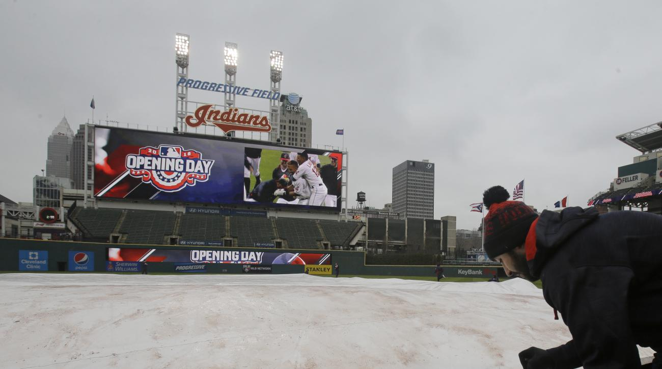 A member of the grounds crew pins the tarp down after a baseball game between the Boston Red Sox and the Cleveland Indians was postponed, Monday, April 4, 2016, in Cleveland. (AP Photo/Tony Dejak)