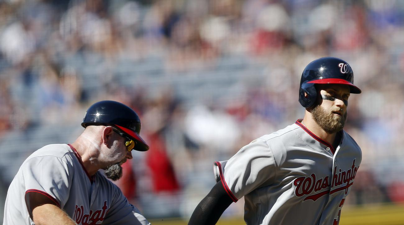 Washington Nationals' Bryce Harper), right, is greeted by third base coach Bob Henley, left, after hitting a solo-home run in the first inning of a baseball game against the Atlanta Braves, Monday, April 4, 2016, in Atlanta. (AP Photo/John Bazemore)