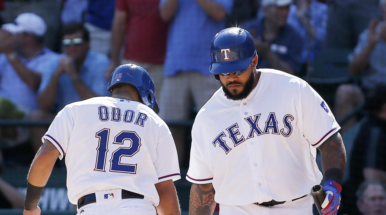 Texas Rangers' Rougned Odor (12) is congratulated by designated hitter Prince Fielder (84) after scoring a run after Shin-Soo Choo was walked with the bases loaded during the fifth inning of a baseball game against the Seattle Mariners, Monday, April 4, 2
