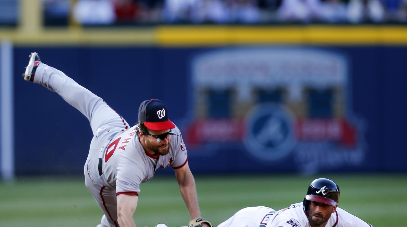 Washington Nationals second baseman Daniel Murphy, left, avoids Atlanta Braves' Nick Markakis, right, while turning a double play on a ground ball hit by Hector Olivera in the seventh inning of a baseball game Monday, April 4, 2016, in Atlanta. (AP Photo/