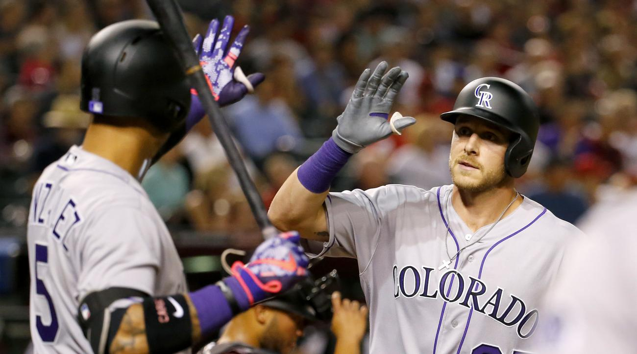 Colorado Rockies shortstop Trevor Story (27) high fives teammate Carlos Gonzalez (5) after hitting his second career home run against the Arizona Diamondbacks during the fourth inning of a baseball game, Monday, April 4, 2016, in Phoenix. (AP Photo/Matt Y