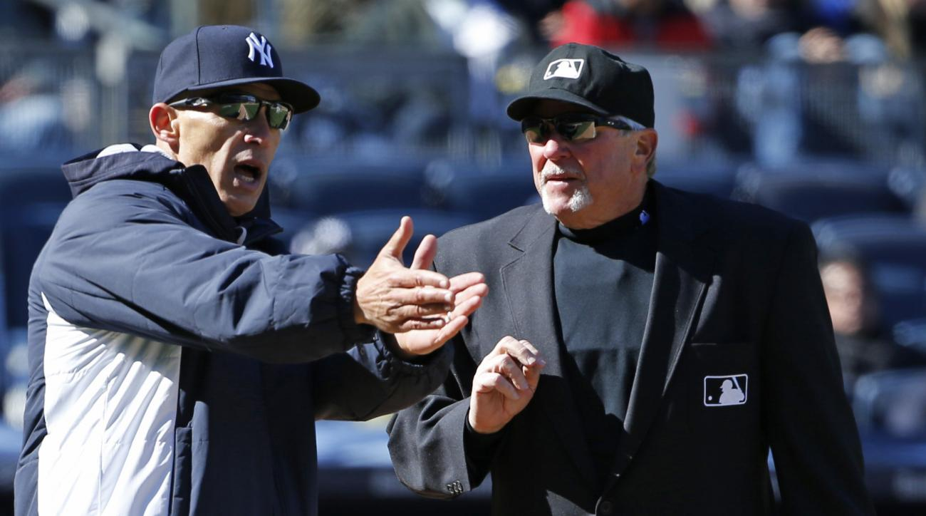 New York Yankees manager Joe Girardi, left, protests to home plate umpire and crew chief Dana DeMuth that Houston Astros shortstop Carlos Correa stayed from the base path and onto the field while running out an infield grounder and blocking Dellin Betance