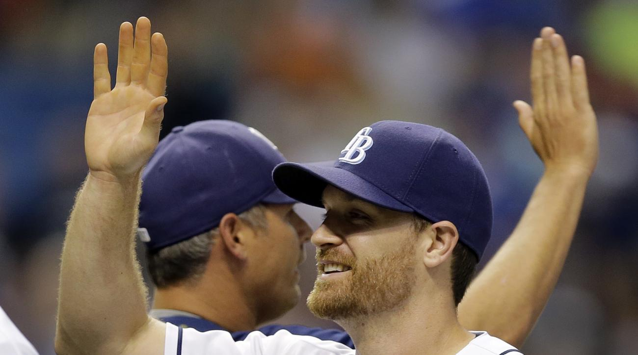 Tampa Bay Rays' Logan Forsythe, front, high-fives manager Kevin Cash after the Rays defeated the Toronto Blue Jays 3-2 during a baseball game Tuesday, April 5, 2016, in St. Petersburg, Fla. (AP Photo/Chris O'Meara)