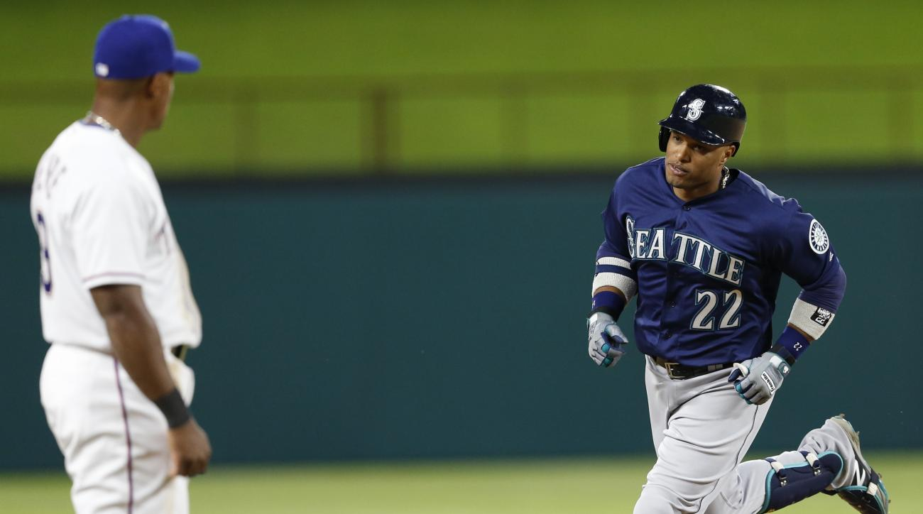 Seattle Mariners' Robinson Cano (22) circles the bases on his home run as Texas Rangers third baseman Adrian Beltre watches during the eighth inning of a baseball game, Tuesday, April 5, 2016, in Arlington, Texas. The Mariners won 10-2. (AP Photo/Jim Cows